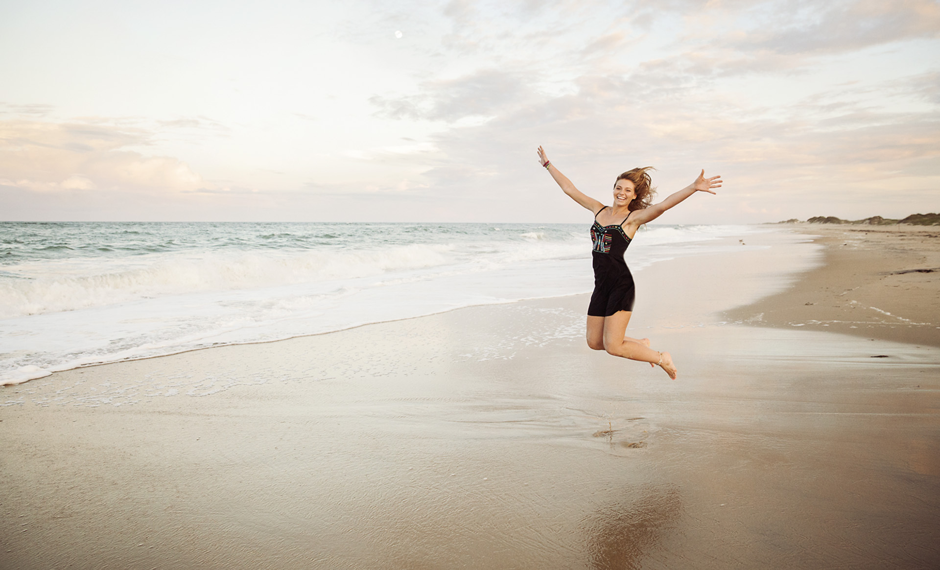 Senior girl jumping by the ocean