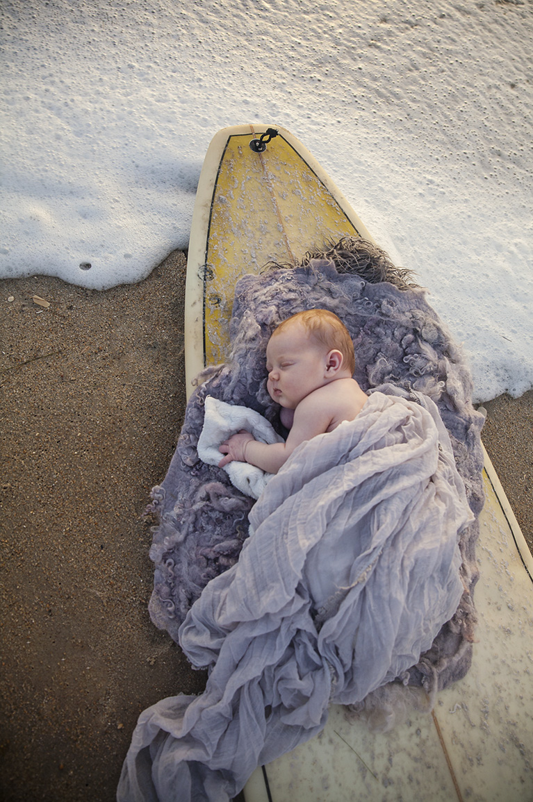 Newborn photo of baby on surfboard in Outer Banks NC