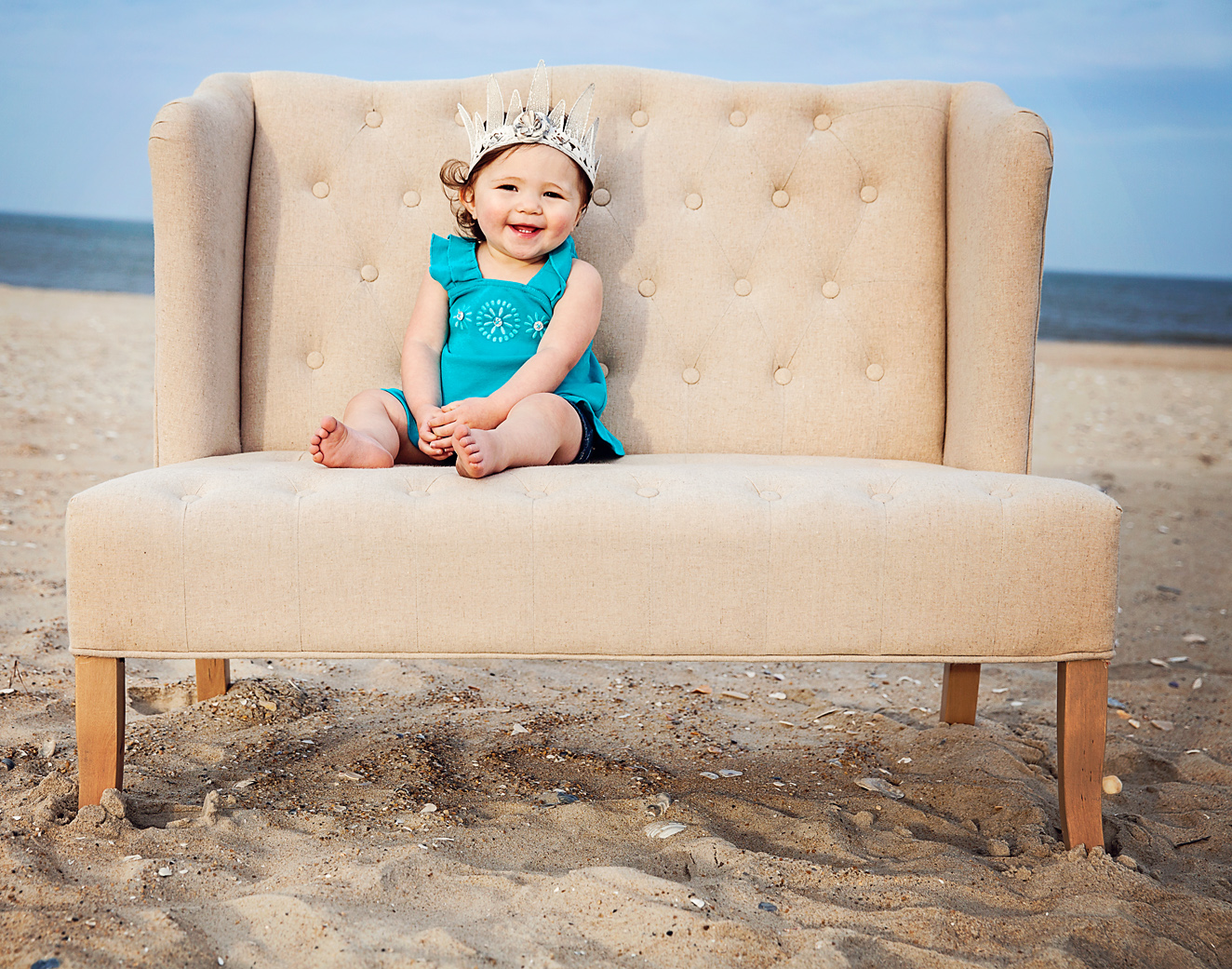 Cute girl with crown sitting on a love seat on the beach in the Outer Banks