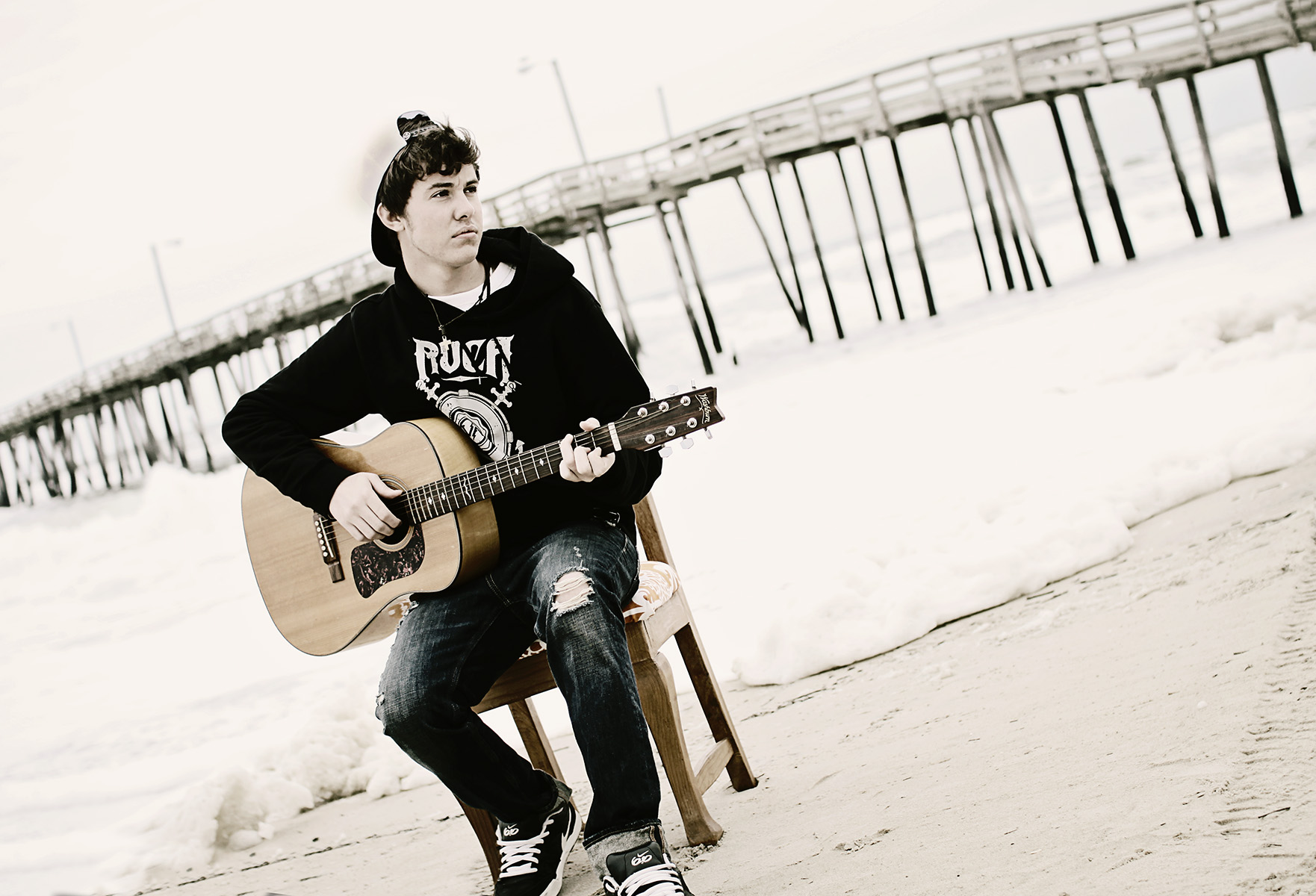 Senior guy playing guitar at the beach