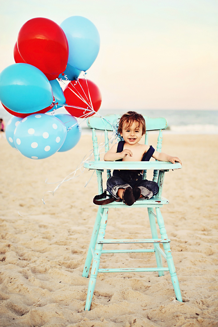 One year old with balloons in a high chair at the beach in NC