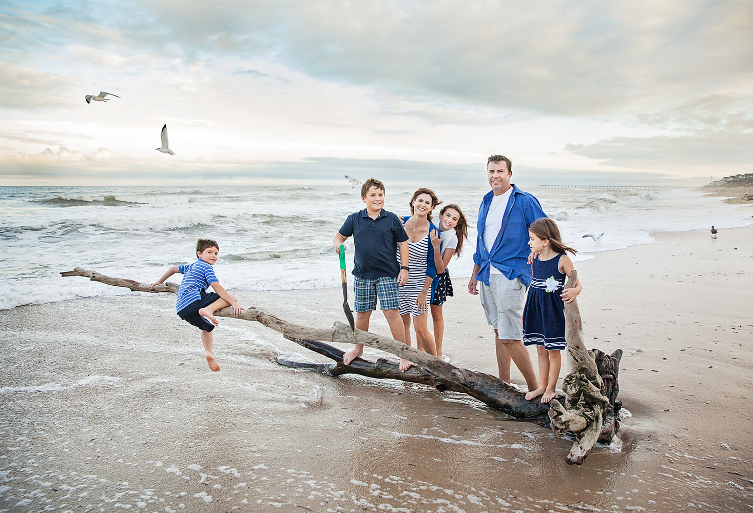 Fun family photo on driftwood on the beaches of Duck NC